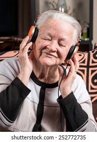 Old woman listening to music in headphones at home
