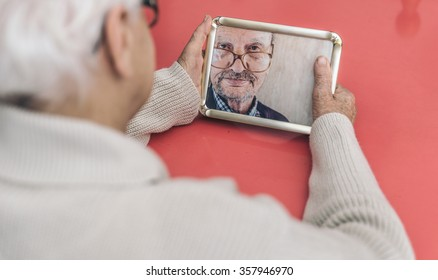 Old woman looking at her husband photo. Widow has nostalgia after a life together