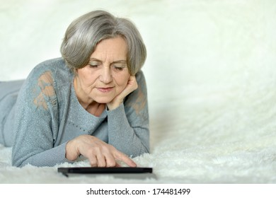 Old woman lying in bed with tablet pc