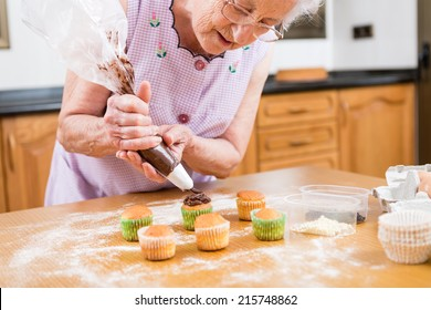 old woman making and decorating cupcakes