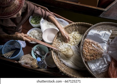 old woman making thai noodle food by sailing in local floating boat market
