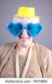 Old woman at masquerade glasses. isolated against grey background
