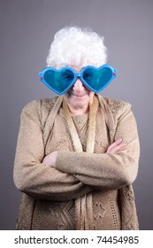 Old woman at masquerade glasses isolated against grey background