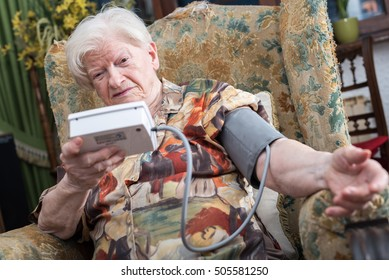 Old woman measuring her blood pressure at home