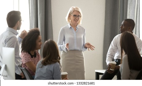 Old woman mentor coach speaker training multicultural interns group explaining team goal at corporate meeting, smiling female leader boss teacher presenting new project to diverse employees in office
