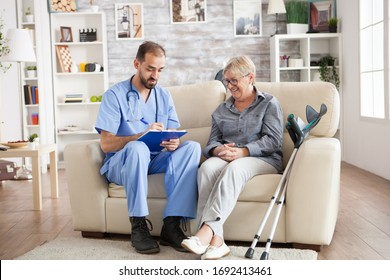 Old woman in nursing home laughing while doctor taking notes on clipboard.