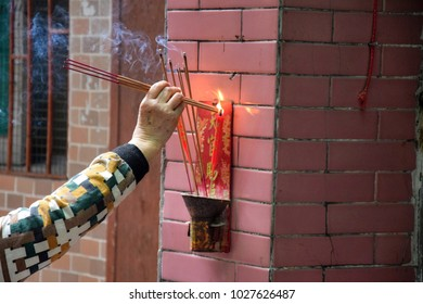 An old woman offers a sacrifice to the Heavenly official.  Burning incenses in front of the sacrificial altar. Translation of the characters is Blessing from a heavenly official.