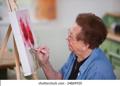 Old woman paints a picture