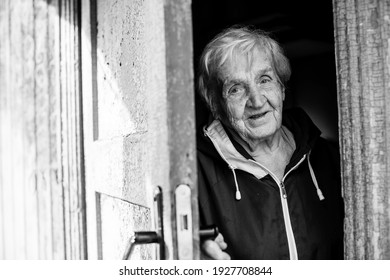 An old woman peeks out from behind the door of his house. Black and white photo.