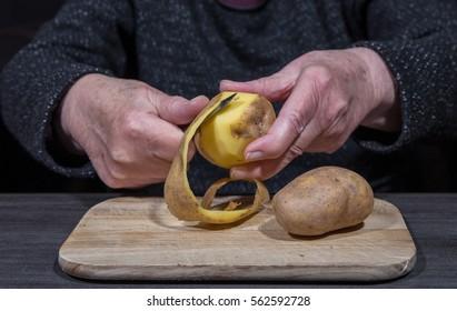 An old woman is peeling potatoes