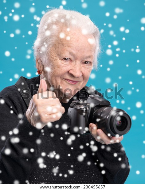 Old woman with photo camera. Christmas and holidays concept