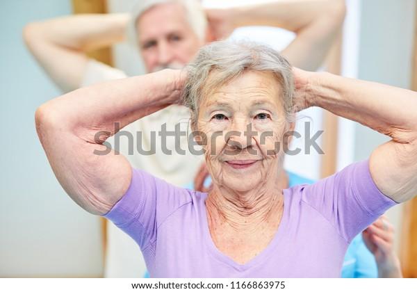 Alte Frau in der Physiotherapie macht gesunde Bewegung in der Rückengymnastik