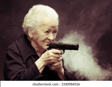 Old woman with pistol on a gray background in studio