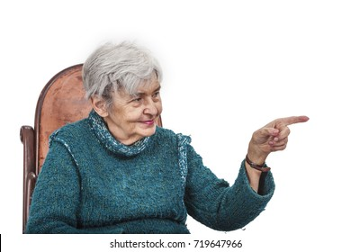 Old woman pointing her left finger to something and looking to it, isolated against a white background.