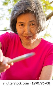 Old woman pointing paintbrush to the camera with happy face.