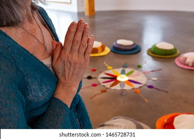 Old woman prays in meditation room. Hands of a religious person are seen closeup, held together as she prays in a peaceful room, twelve colors of the Native American circle are seen in background.