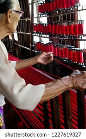 old woman preparing silk threads for weaving loom