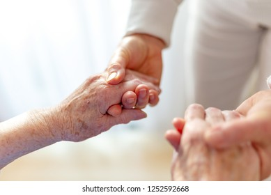 old woman reaches for her nurse's hands
