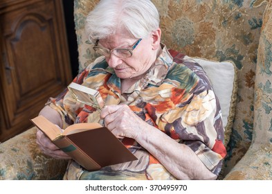 Old woman reading a book with a magnifying glass