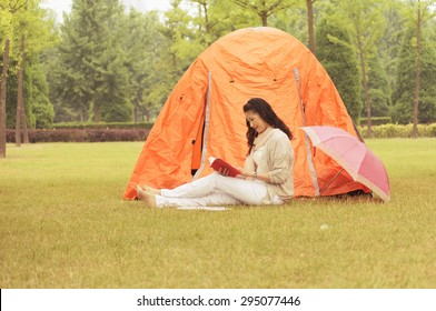Old woman reading a book. Next to a tent on the lawn