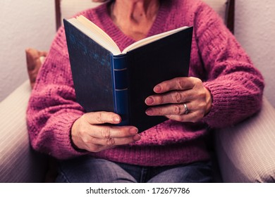 Old woman reading at home