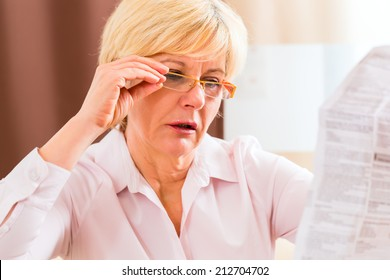 Old woman reading  medicament package insert at home with glasses