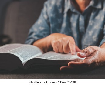 Old woman reading thick book at home. Grandmother with Bible. Concentrated elderly pensioner with wrinkles on hands attentively follows finger on paper page in library.