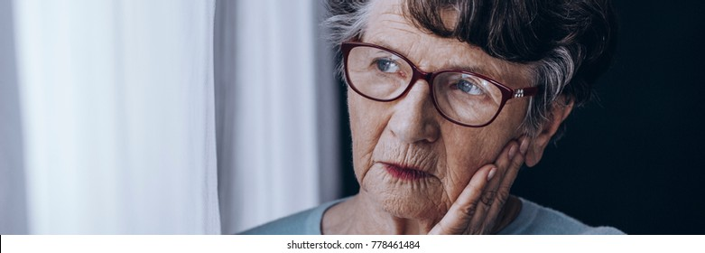 Old woman in red glasses looking through the window, mourning the loss of her relative