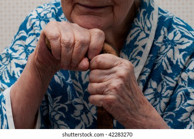 An old woman rests her chin on her stick closeup