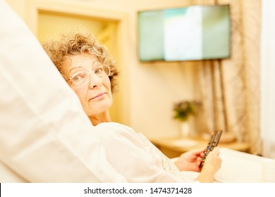 Old woman in retirement home or senior citizen apartment lies in bed watching tv