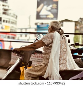 An old woman is riding a bike in the city streets of Bangalore unique photo