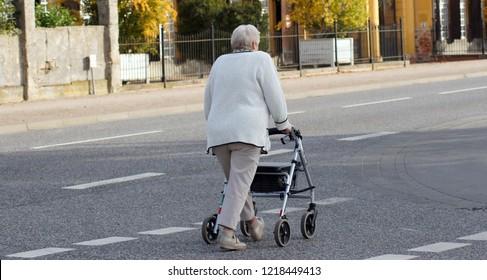 Old woman with rollator crosses the street