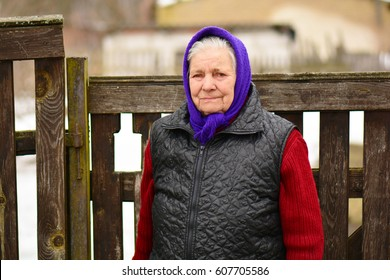 The old woman in the russian winter village near fence.