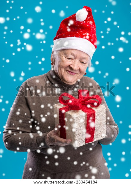 Old woman in santa hat with gift box. Christmas and holidays concept