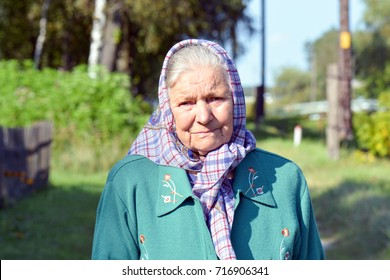 An old woman in a scarf. Portrait of a lonely old woman standing in a village