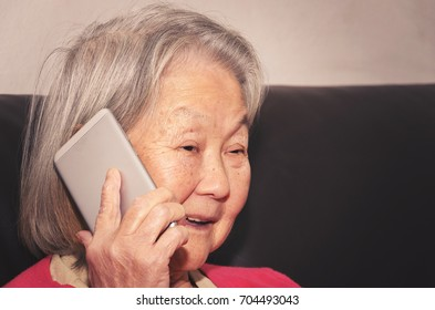 Old woman seated on a sofa at home holding a smartphone into the ear on a phone call. Old woman talking happy on the phone.