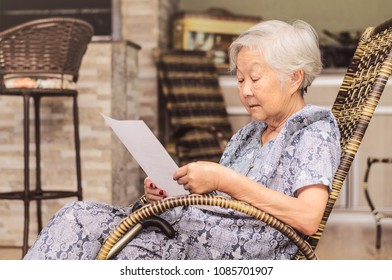 Old woman seated reading carefully a document or terms of a insurance. Old obaasan (grandma), japanese descendant.