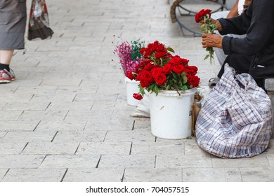 old woman selling flowers on street