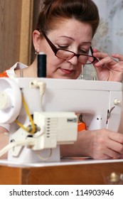 old woman sews clothes in-home