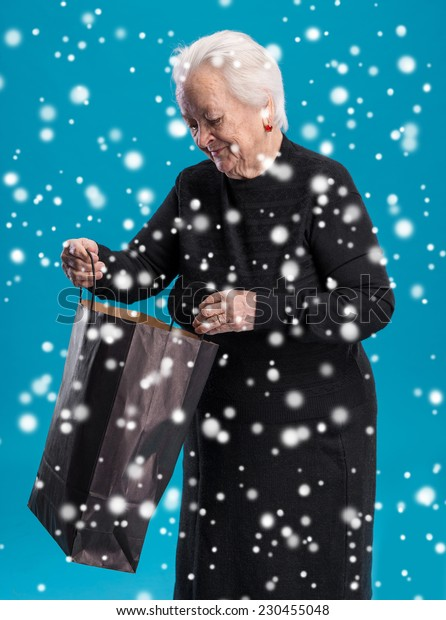 Old woman with shopping bag. Christmas and holidays concept