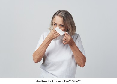 an old woman with a short haircut blows out in a napkin, runny nose health problems