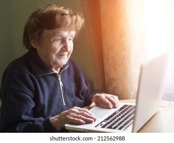 Old woman sing laptop computer at home.