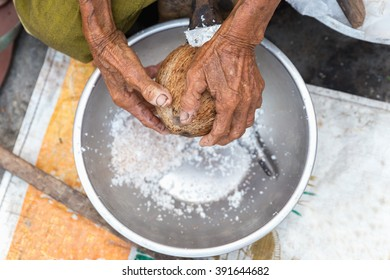 Old woman sit on coconut grater and grate coconut into bowl in morning market for sale