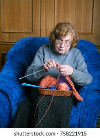The old woman sits in an armchair knitting