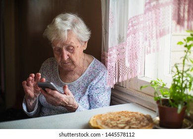 Old woman sits at home and use smartphone.