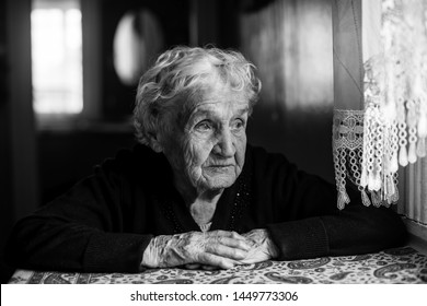 An old woman sits in a house near the window. Contrast black and white portrait.
