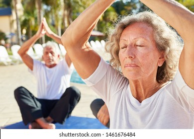 Old woman sits and meditates in the spa by the pool in a yoga class or workshop