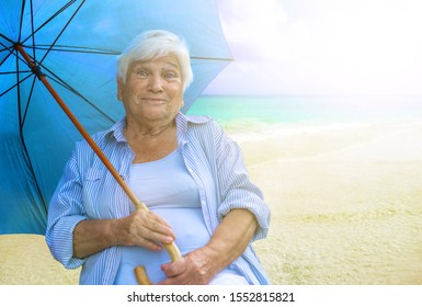 an old woman sits on the beach with an umbrella. Hiding from the sun