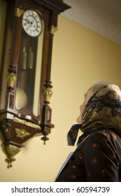Old woman sitting in front of a big old clock. Focus on the woman's head. See more images.