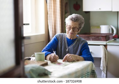 Old woman is sitting in her country style kitchen